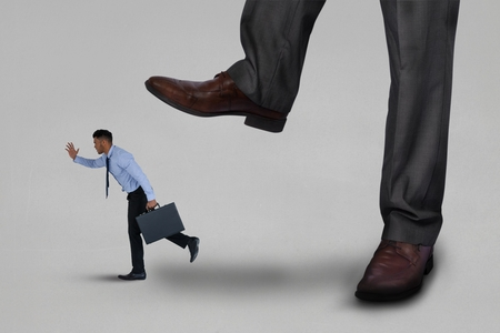 brogues: Digital composite of Big business man trying to step on a small business man running