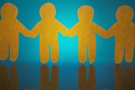 4 yellow paper person holding hands against blue background Stock Photo