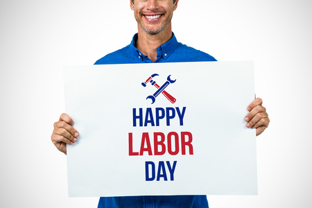 Portrait of happy man holding placard against digital composite image of happy labor day text with tools