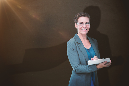 Business woman against blackboard