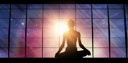 Silhouette image of female practicing meditation against illuminated empty room with window