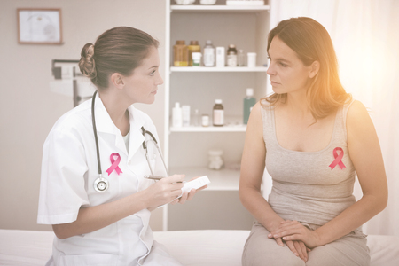Breast cancer awareness ribbon against doctor taking notes
