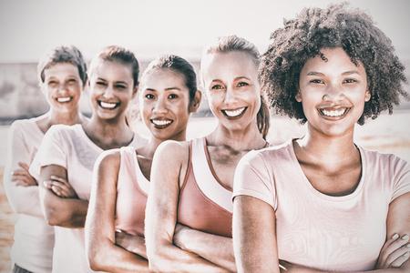 retrato de mujeres sonrientes que usan rosa para el cáncer de mama con los brazos cruzados en el parque