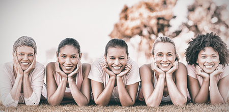 Portrait of smiling women lying in a row for breast cancer awarness in park 스톡 콘텐츠