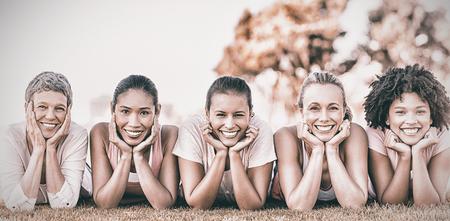 Portret van glimlachende vrouwen die op een rij voor awarness van borstkanker in park liggen