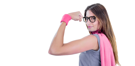 Portrait of confident woman in superhero costume while flexing muscles on white background