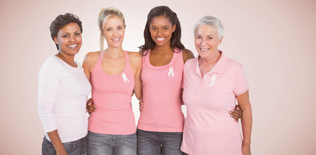 Portrait of happy women supporting breast cancer social issue against neutral background Standard-Bild
