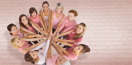 Portrait of happy female friends supporting breast cancer awareness against white wall 版權商用圖片