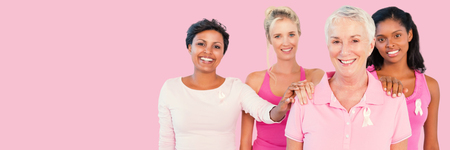 Portrait of women supporting breast cancer awareness against pink background Stock Photo