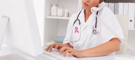 Breast cancer awareness message against concentrated doctor using computer and telephone Stock Photo