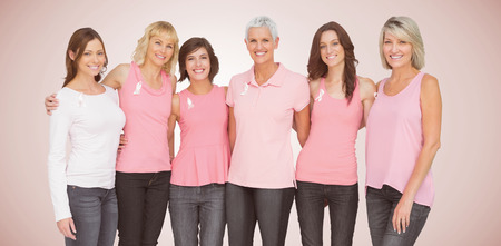 Portrait of smiling women supporting breast cancer social issue against neutral background 스톡 콘텐츠