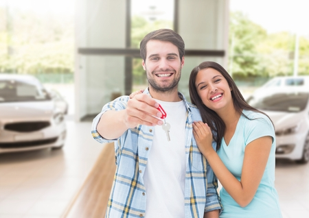 Digital composite of Couple  Holding key in front of cars