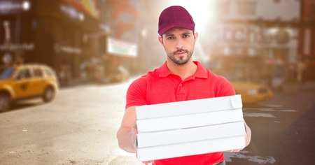 delivery service: Digital composite of Delivery man with pizza boxes against blurry street with flare