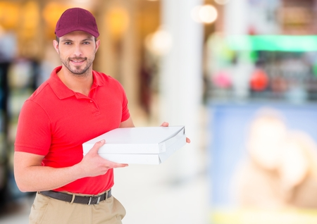 shopping binge: Digital composite of Delivery man with pizza box against blurry shopping centre Stock Photo