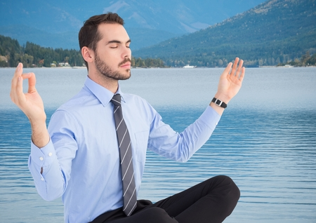 Digital composite of Business man meditating against river and hills with trees