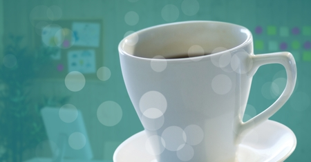 monitor: Digital composite of White coffee cup on saucer with bokeh against blurry office with teal overlay
