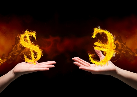 Digital composite of hand with dolar fire icon over and hand with euro fire icon over. Black and red (fire) background Stock Photo