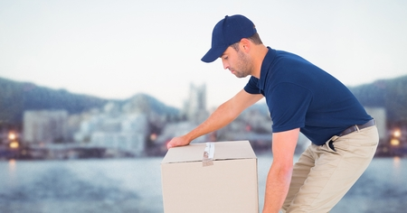 Digital composite of Delivery man picking up box against blurry skyline Stock Photo