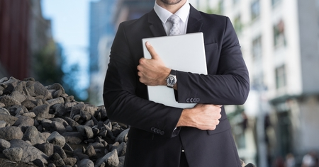 Digital composite of Rubble stones in city with businessman holding laptop