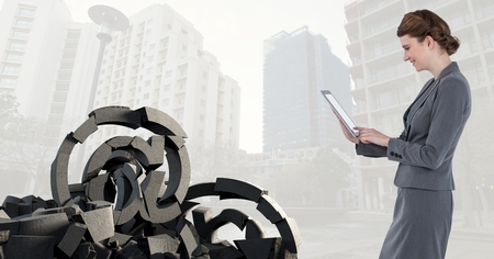 Digital composite of Broken concrete stone with at symbol and businesswoman in cityscape