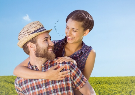 Digital composite of Couple piggy back in field on summer day