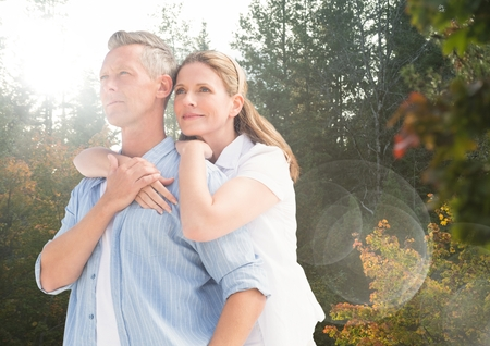 innumerable: Digital composite of Middle aged couple embracing in forest with flare