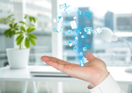 Digital composite of hand with application blue icons coming up form it. Blurred office background Stok Fotoğraf