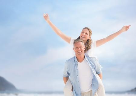 Composite numérique de couple de personnes âgées moyenne branche contre le ciel floue et la plage Banque d'images - 85950284