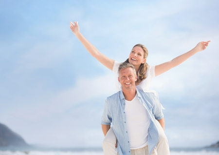 Digital composite of Middle aged couple piggy back against blurry sky and beach