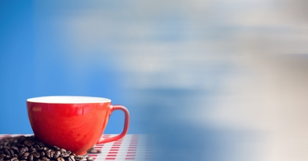 Digital composite of Red coffee cup on red and white table cloth with beans against blue background and blurry sky transi