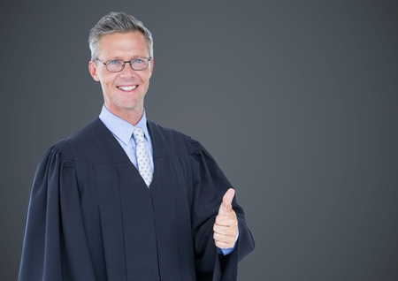 house robes: Digital composite of Male judge thumbs up against grey background