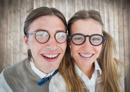 Digital composite of Close up of nerd couple against blurry wood panel with grunge overlay Stock Photo