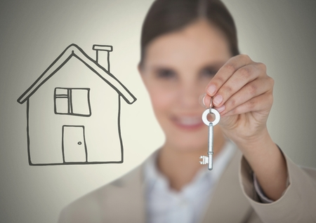 Digital composite of Woman Holding key with house drawing in front of vignette Stock Photo