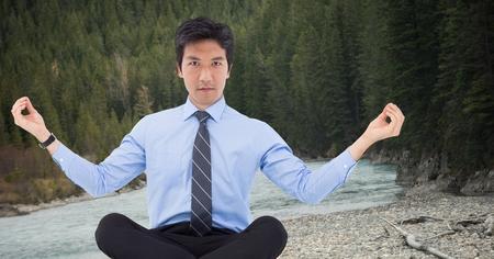 Digital composite of Business man meditating against river