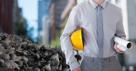 Digital composite of Rubble stones with Architect Construction worker holding helmet and blueprints in city