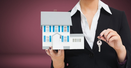 Digital composite of Woman Holding key and house in front of vignette Stock Photo