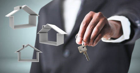Digital composite of Hand Holding key with home icons in front of vignette Stock Photo