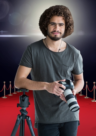 Digital composite of photographer rest on tripod, with the camera on hands in the red carpet. Flares behind Stock Photo