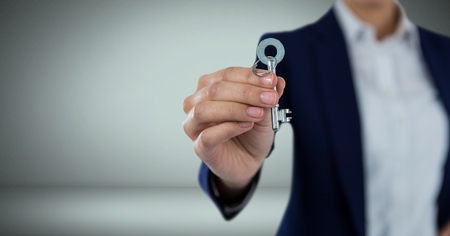 Digital composite of Hand holding key in front of Vignette Stock Photo