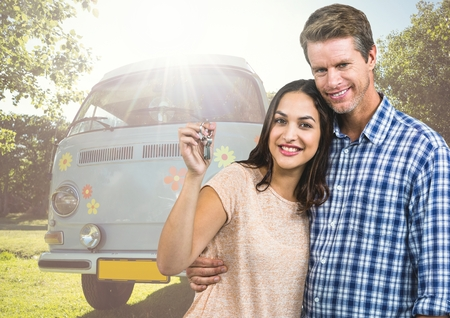Digital composite of Couple holding keys in front of Camper van