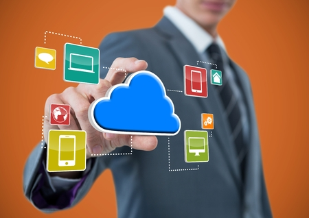 Digital composite of businessman with hand spread of  taking cloud with application icons. Orange background Stock Photo