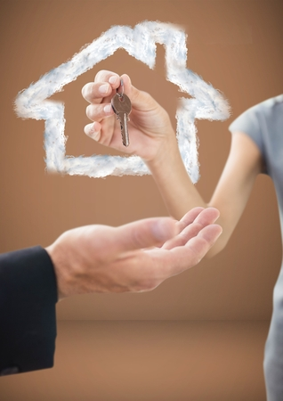 Digital composite of Hands Holding key with house icon in front of vignette