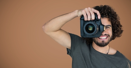 Digital composite of Millennial man with camera against brown background