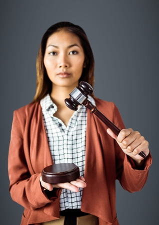 Digital composite of Female judge with gavel against grey background Stock Photo