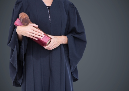 Digital composite of Female judge mid section with book and gavel against grey background