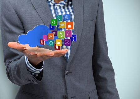 Digital composite of Business hand spread of with cloud and application icons. Light blue background