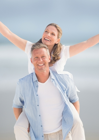 Digital composite of Middle aged couple piggy back against blurry beach Stock Photo