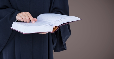 Digital composite of Judge mid section with open book against brown background