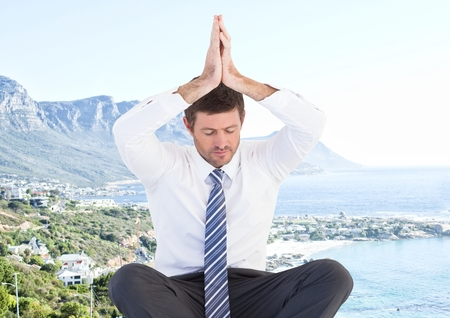 Digital composite of Business man meditating against blurry coastline