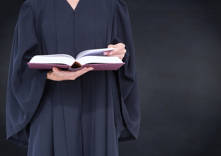 Digital composite of Female judge mid section with open book against navy chalkboard
